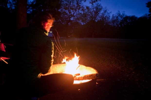 woman stoking fire at dusk, brazos bend state park, texas