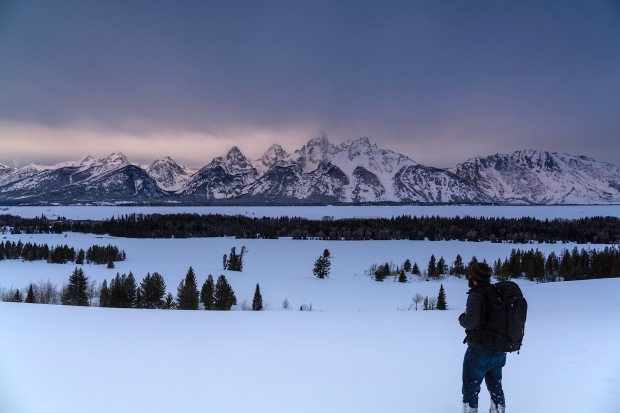 Lone male hiker looking out in the snow toward the tetons