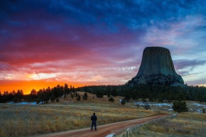 a lone hiker enjoys a dramtic sunrise over Devils tower national monument, WY