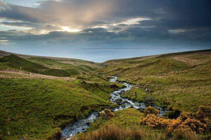 The River Abhainn An Lethuillt with wildflowers and dramatic morning light and clouds