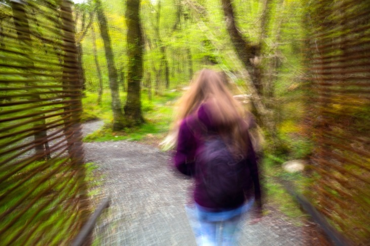 A woman in motion hiking on the Falls of Falloch trail