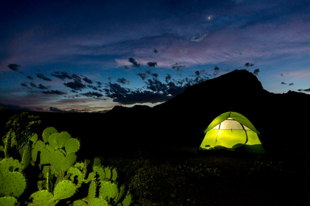 Dusk, colorful sky, and lit tent under a silhouetted Nugent Mountain