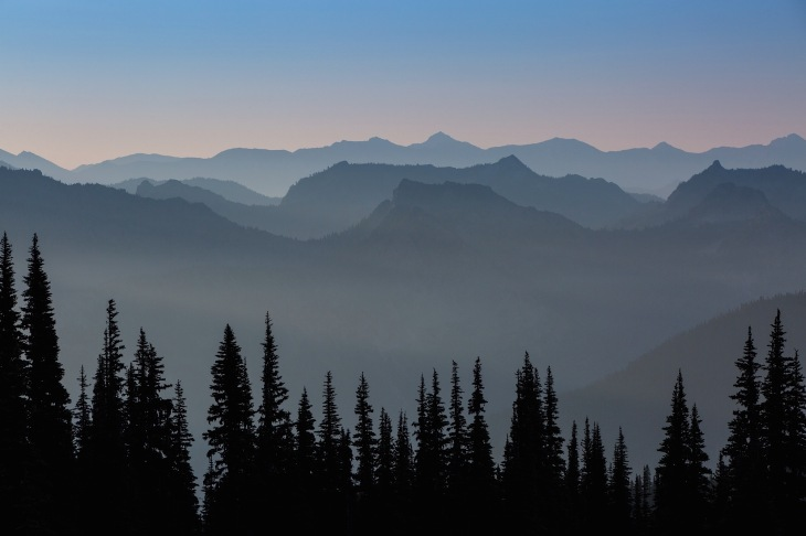 sunrise over the peaks surrounding mt. rainier