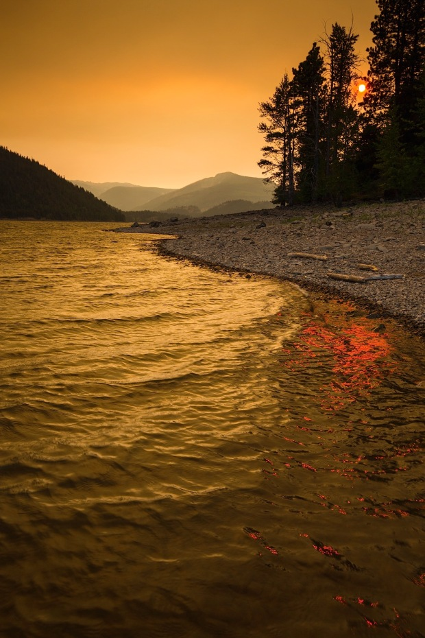 An eerie sunset over Rimrock Lake near Mount Rainier casts yellow and red from the nearby forest fires