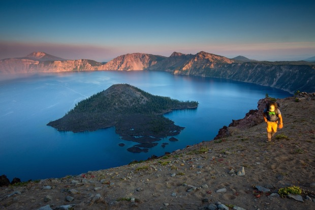 A man hiking the rim at sunset in Crater Lake National Park