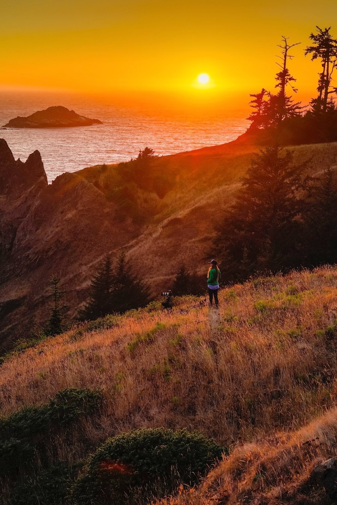 The sun sets on the Pacific and a tent campsite with beautiful displays of color