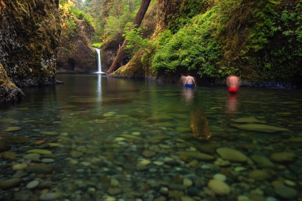 Two men wade to get a closer look at Punchbowl Falls