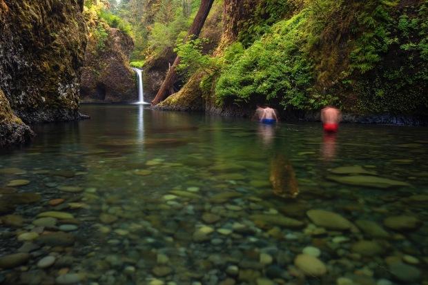 Two men wade to get a closer look at Punchbowl Falls