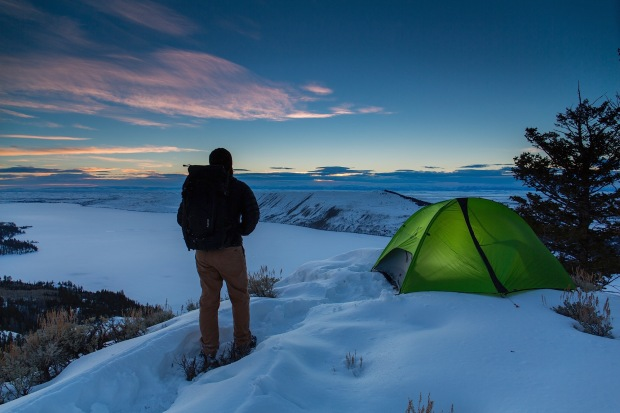 Man hiking up to a winter campsite overlooking Fremont Lake in Bridger National Forest, Wy