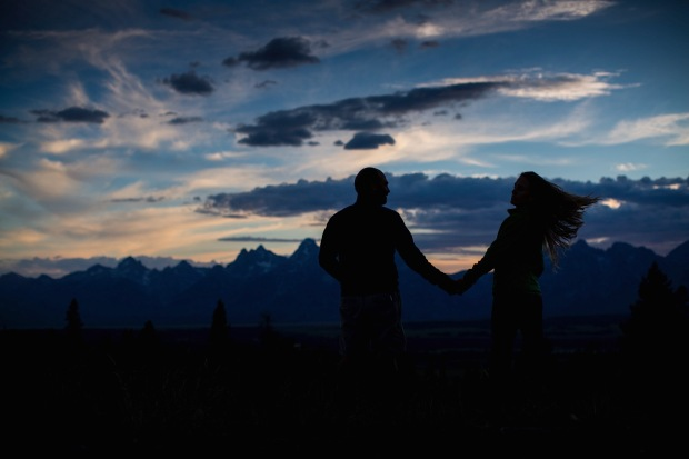 silhouette of a man and woman holding hands at dusk with the Tetons in the background