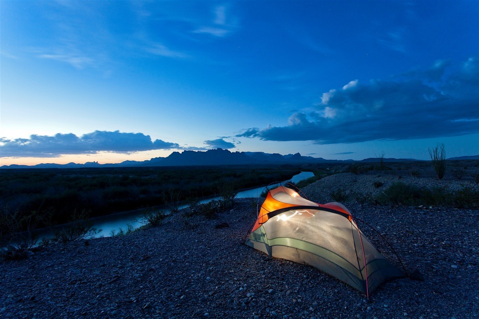 tent camping at dusk on the rio grande and the chisos mountains in big bend national park, texas