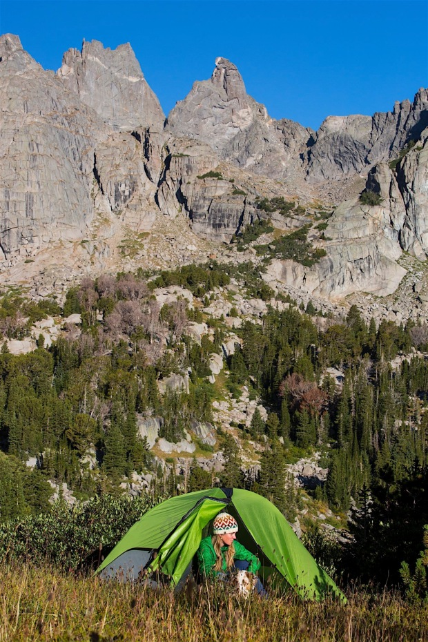 A woman emerging from her tent with her dog at the Cirque of the Towers in the southern Winds